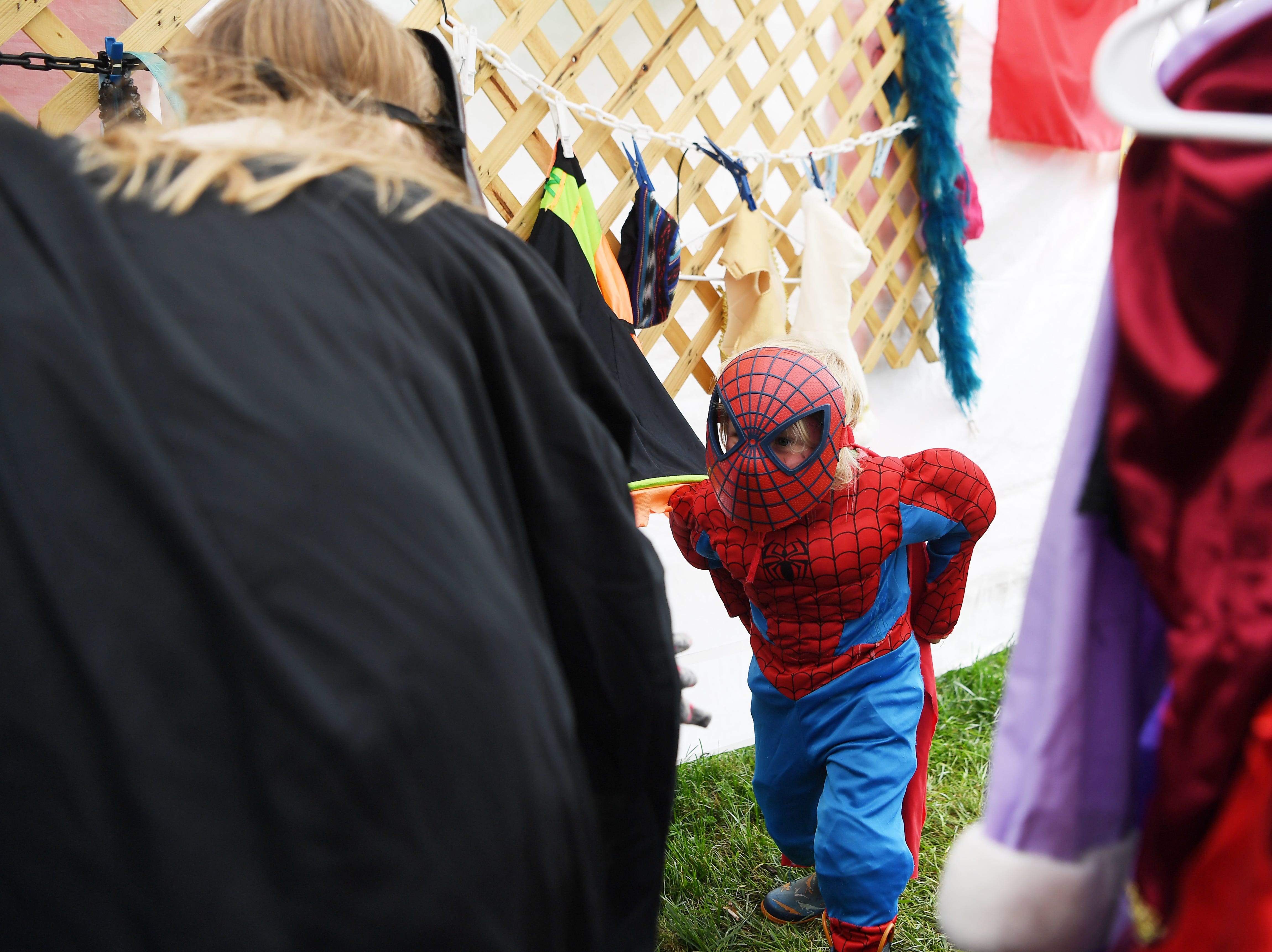 Jade McDowell, 4, acts like Spiderman as he plays with LEAF volunteer Haddie Herr in the costume tent at the 47th Lake Eden Arts Festival in Black Mountain Oct. 20, 2018.