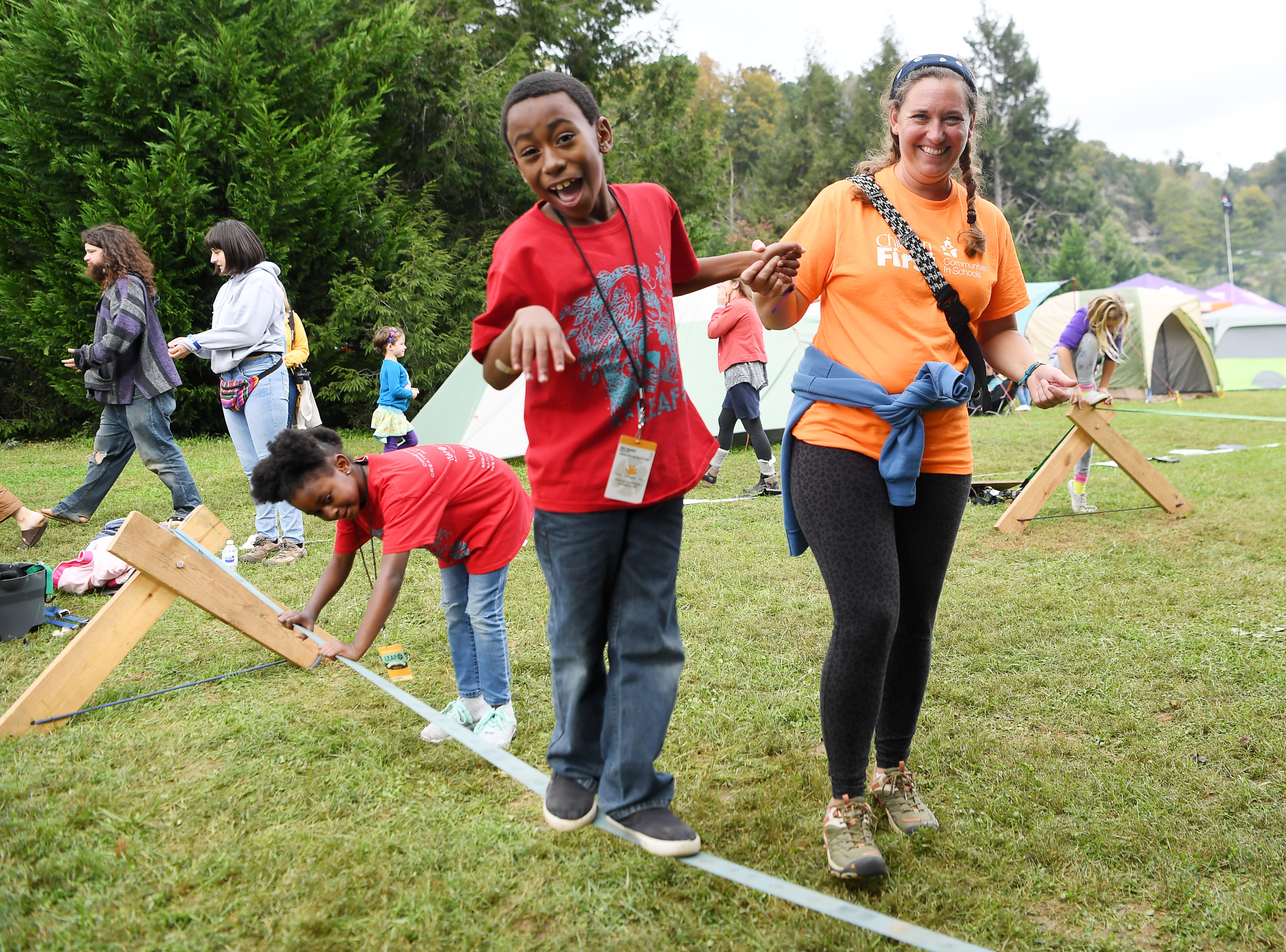 Zion Wright, 8, walks across a slack line with help from Whitney Campassi at the 47th Lake Eden Arts Festival in Black Mountain Oct. 20, 2018.
