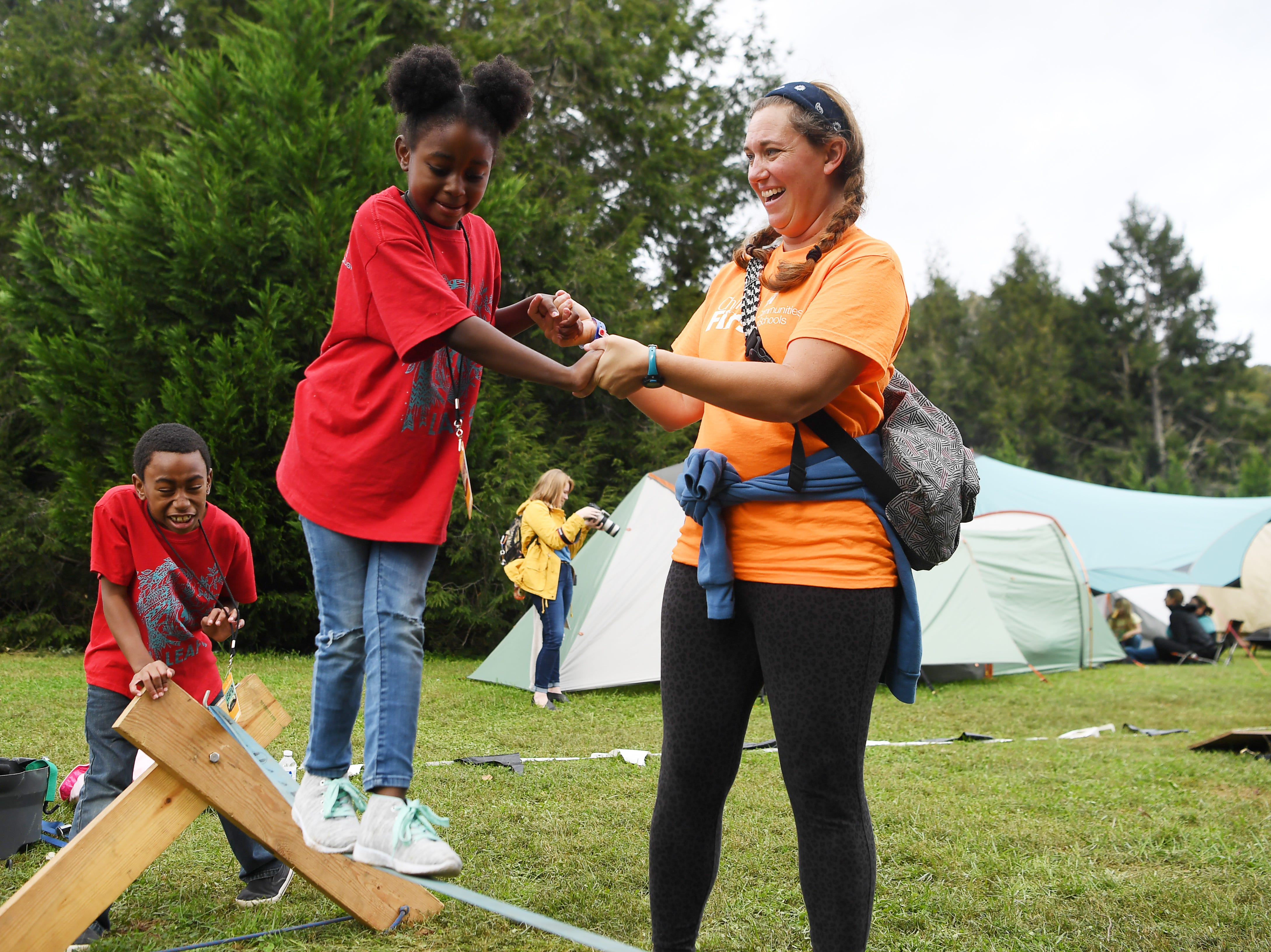 Tiraji Wright, 6, walks across a slack line with help from Whitney Campassi at the 47th Lake Eden Arts Festival in Black Mountain Oct. 20, 2018.