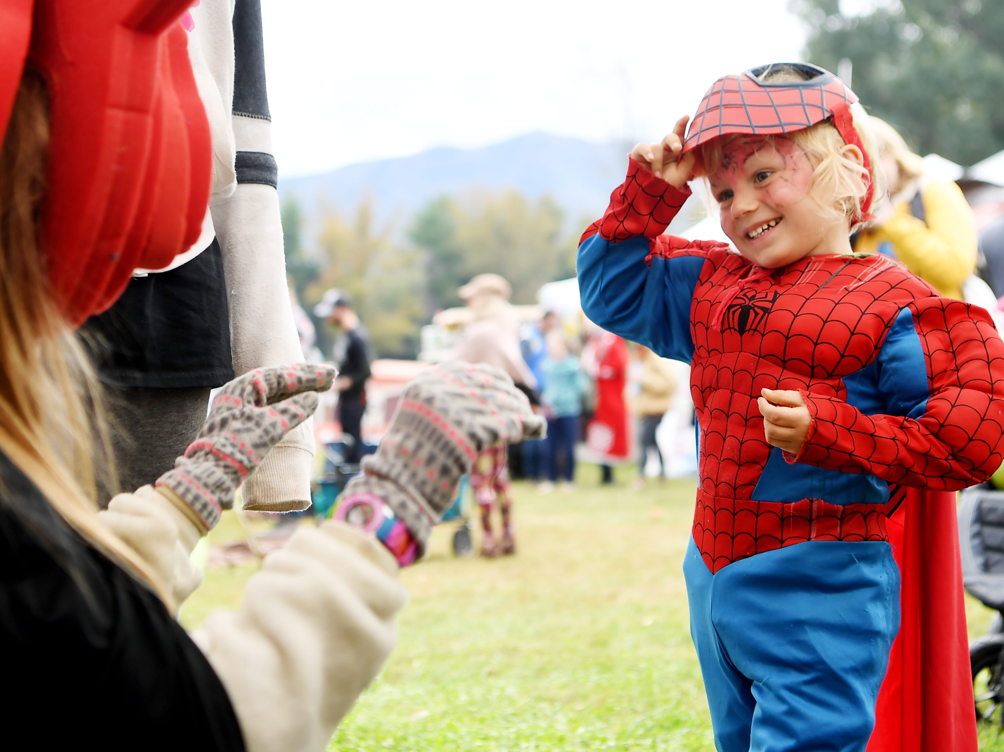Jade McDowell, 4, lifts his Spiderman mask in the costume tent as he plays with volunteer Haddie Herr, 12, at the 47th LEAF Festival at Lake Eden in Black Mountain Oct. 20, 2018.