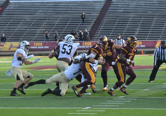 Central Michigan quarterback Tommy Lazzaro is sacked by Western Michigan linebacker Najee Clayton (7) during the third quarter of play at Kelly/Shorts Stadium in Mt. Pleasant on Saturday, October 20, 2018.