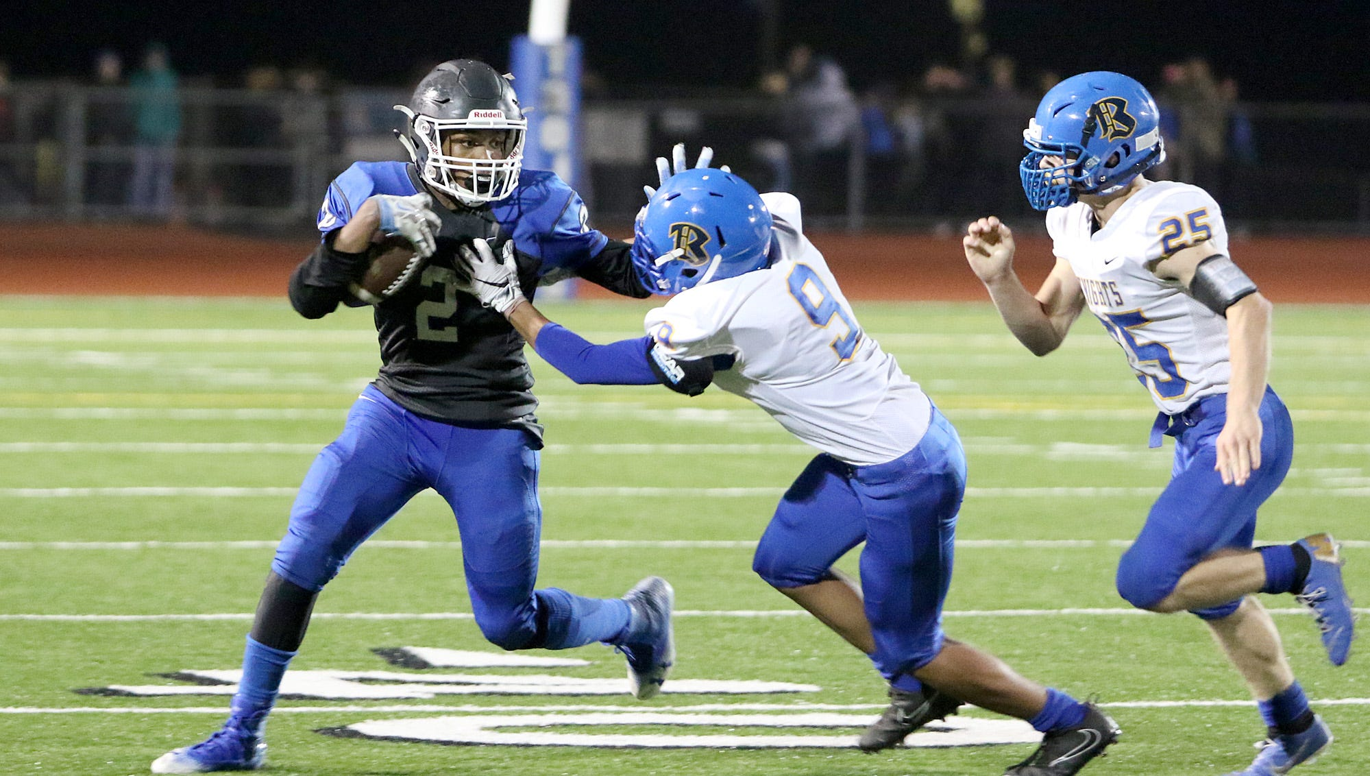 Olymic's Darelle White fights off Bremerton's Hector Infante and Ryan Saylor during the Trojans' 34-27 win Friday night at Silverdale Stadium.