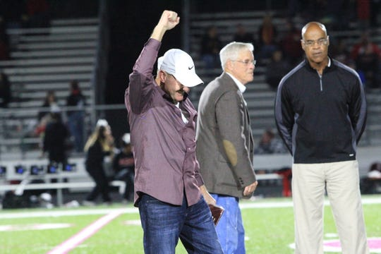 Kenny Ford pumps his fist at midfield after being introduced to the crowd as a Hall of Fame inductee at halftime.
