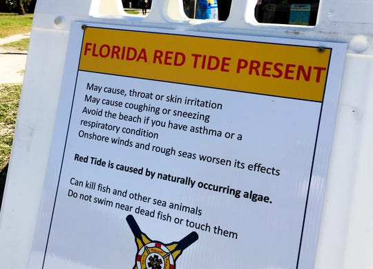 Signs warn of red tide effects at Lori Wilson Park in Cocoa Beach.
