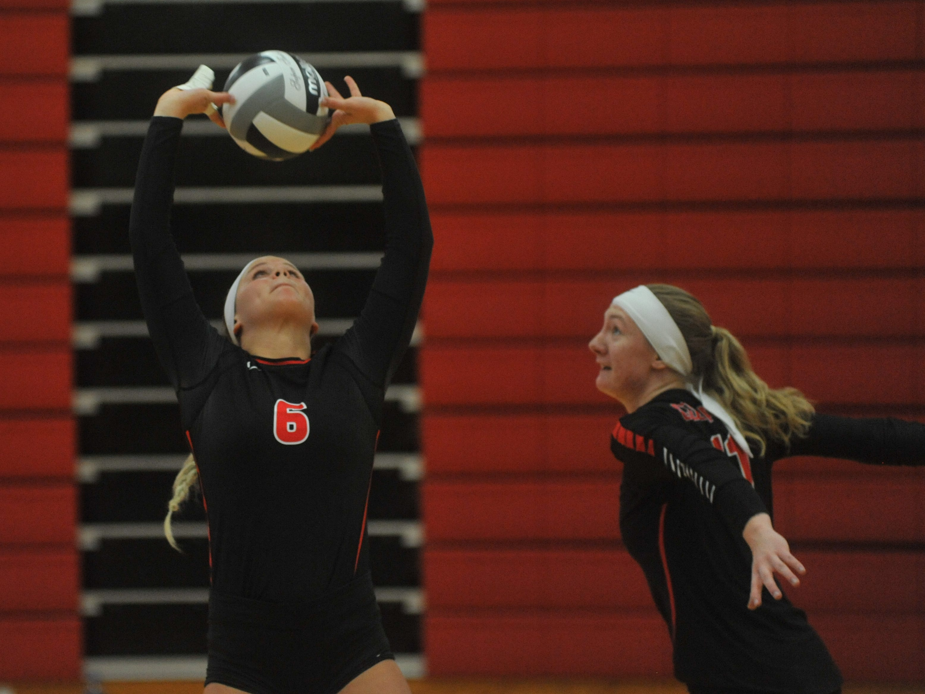 Crestview's Magey Shambre sets teammate Autumn Bailey at the net.