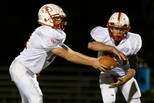 Rutland quarterback Ryan Moore (11) hands the ball off to Dakota Peters (33) during the high school football game between the Rutland Raiders and the Burlington/South Burlington SeaWolves at Buck Hard Field on Friday night October 19, 2018 in Burlington.
