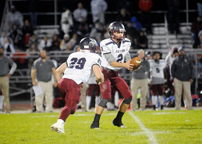 Eastern's QB, Andrew Heck, hands the ball off to TJ Franden for a short gain against Hammonton on Friday, October 19, 2018.