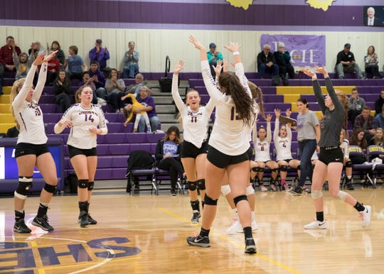 The Lady Shermans celebrate after scoring against Vinton County during their third and final set of their sectional final game against Vinton County.