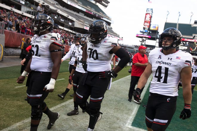 Cincinnati Bearcats linebacker Joel Dublanko (41) and Cincinnati Bearcats offensive lineman Dino Boyd (70) walk to the locker room after the NCAA football game between Cincinnati Bearcats and Temple Owls on Saturday, Oct. 20, 2018, at Lincoln Financial Field in Philadelphia, Penn. Cincinnati Bearcats lost to Temple Owls in overtime 17-24.