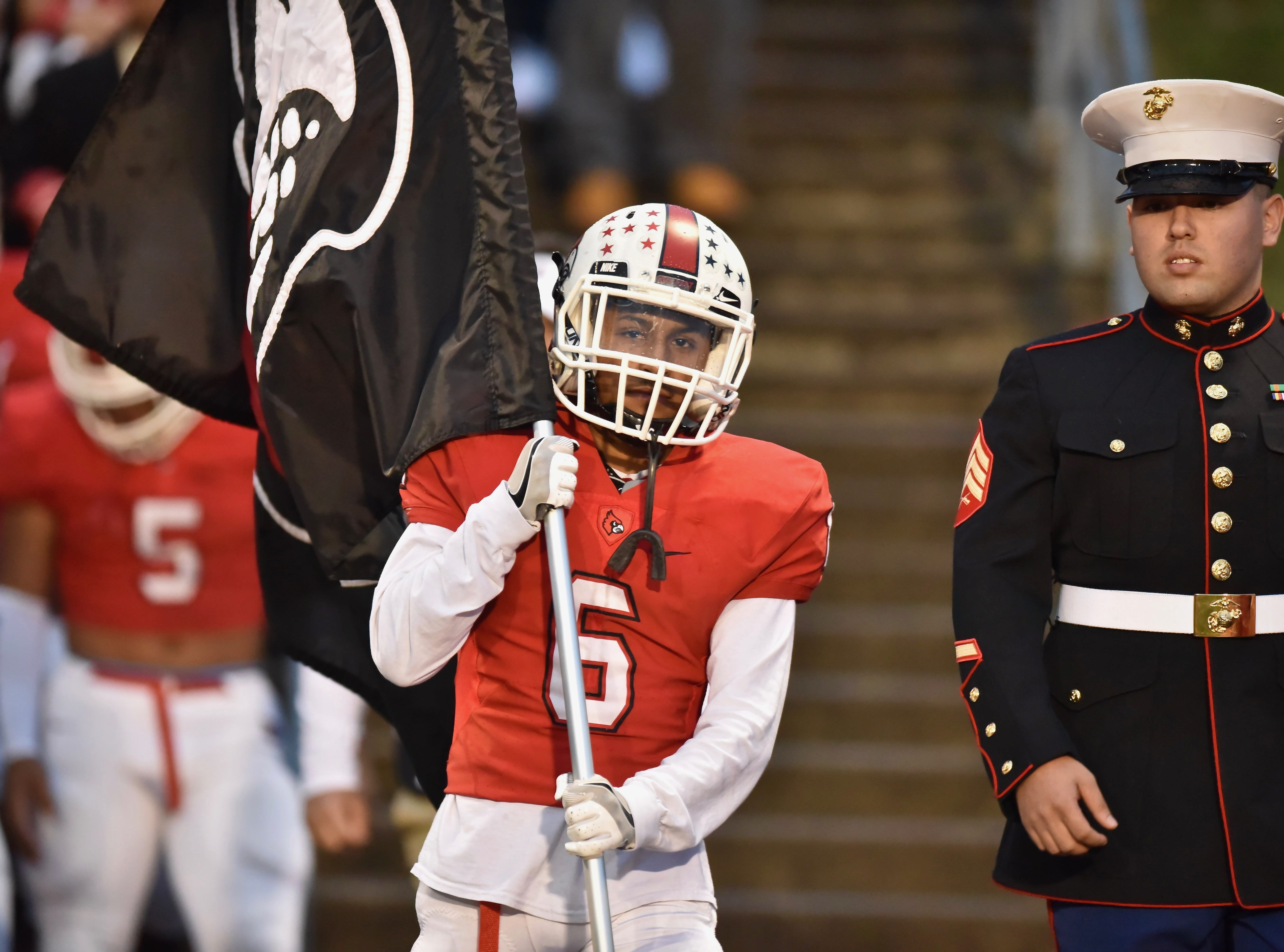 Colerain's Hector Lopez leads the Cardinals onto the field Friday, Oct. 19, 2018 at Colerain High School