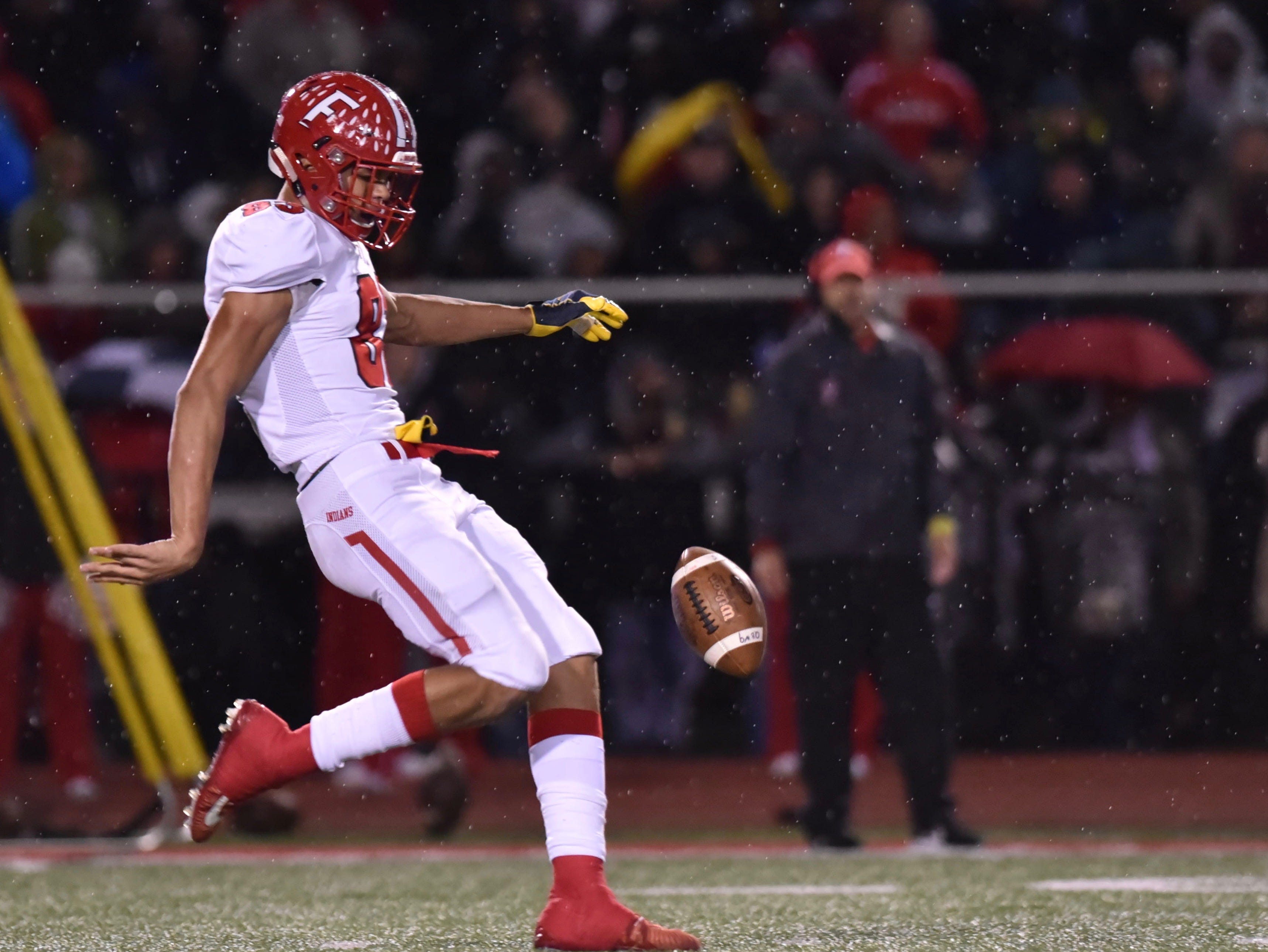 Fairfield's Erick All punts the ball against Coelrain as the rain began to fall Friday, Oct. 19, 2018 at Colerain High School