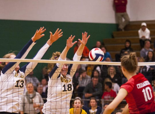 Notre Dame Academy's Belle Morgan and Abby Powers put up strong defense against St. Henry's Zoe Epplen in the Ninth Region final Oct. 18.