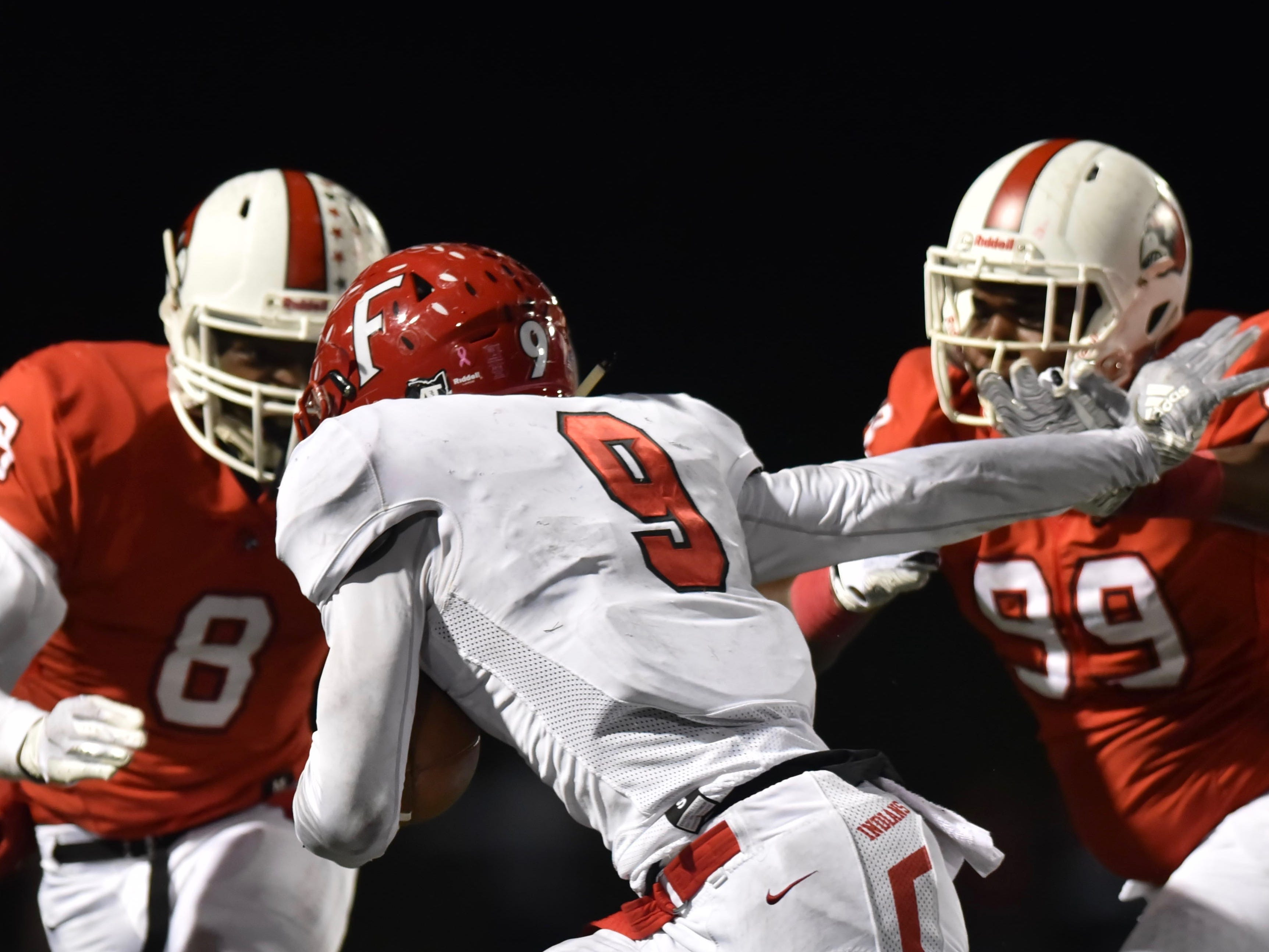 Fairfield's Jutahn Mcclain tries to elude the Cardinals' Jakari Patterson and Eric Phillips Friday, Oct. 19, 2018 at Colerain High School