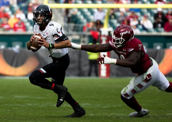 Cincinnati Bearcats quarterback Desmond Ridder (9) runs away from Temple Owls defensive tackle Michael Dogbe (9) during the NCAA football game between Cincinnati Bearcats and Temple Owls on Saturday, Oct. 20, 2018, at Lincoln Financial Field in Philadelphia, Penn.