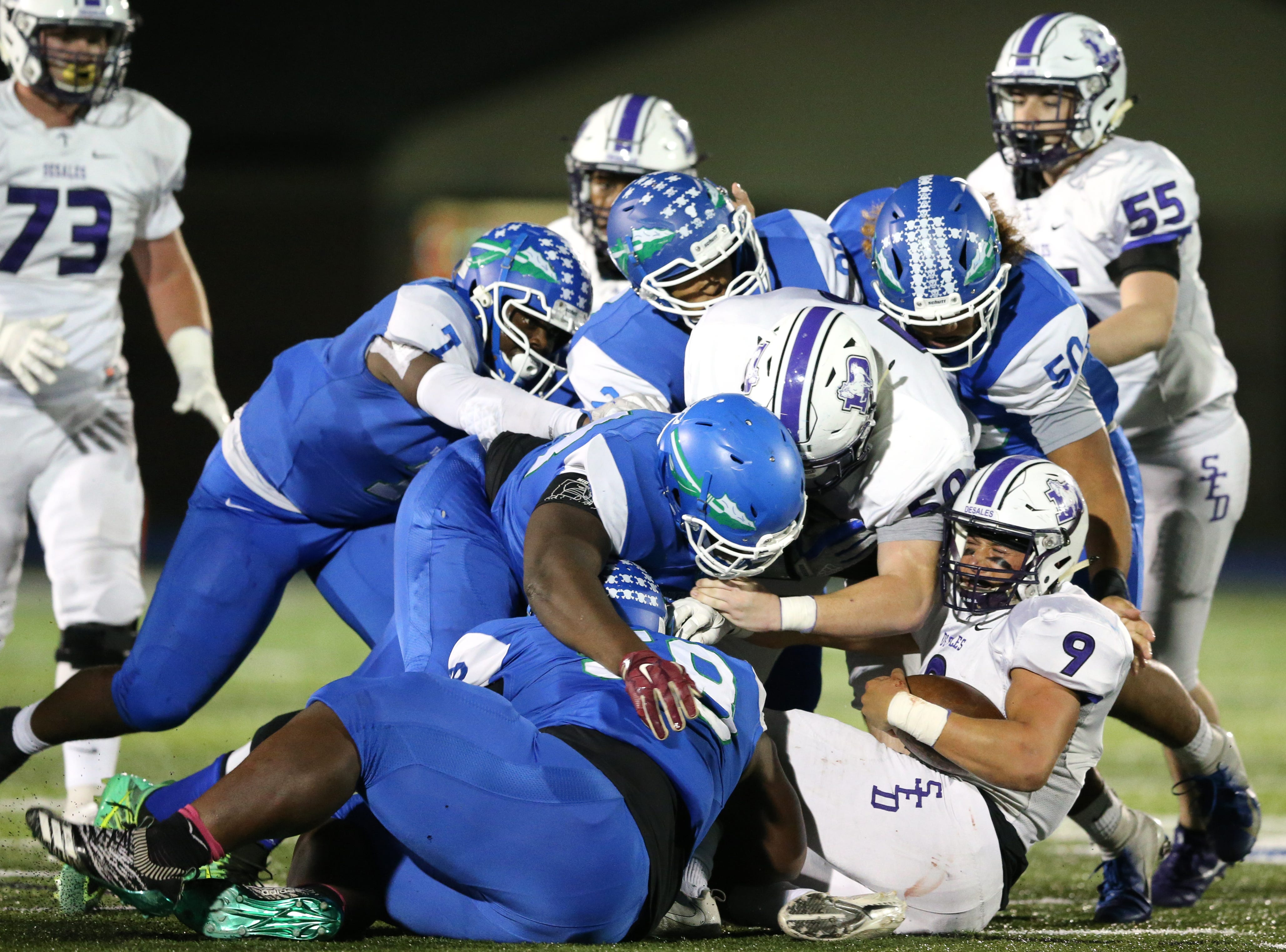 The Winton Woods Warriors defense gang tackles St. Francis de Sales Stallions quarterback Joey Velazquez (9) in the second quarter during a high school football game between St. Francis de Sales and Winton Woods, Friday, Oct. 19, 2018, at Winton Woods High School in Forest Park, Ohio.