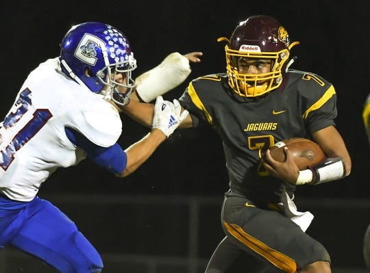 Cooper quarterback Jeremiah Lee stiff arms a Conner defender in the Skyline Chili Crosstown Showdown at Cooper High School, Union, KY, Friday Oct. 19, 2018