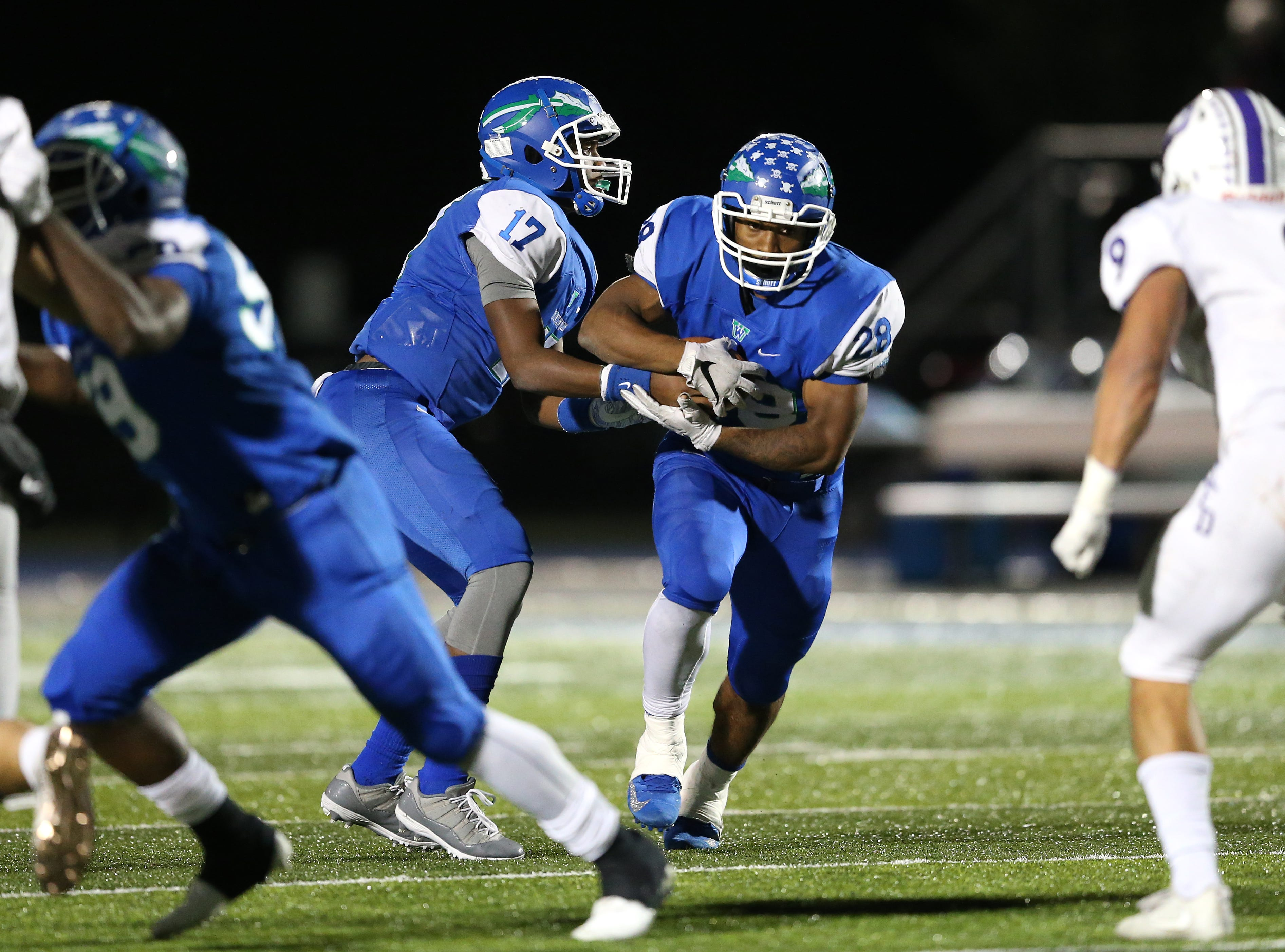 Winton Woods Warriors quarterback MiChale Wingfield (17)  hands the ball off to running back Miyan Williams (28) in the second quarter during a high school football game between St. Francis de Sales and Winton Woods, Friday, Oct. 19, 2018, at Winton Woods High School in Forest Park, Ohio.