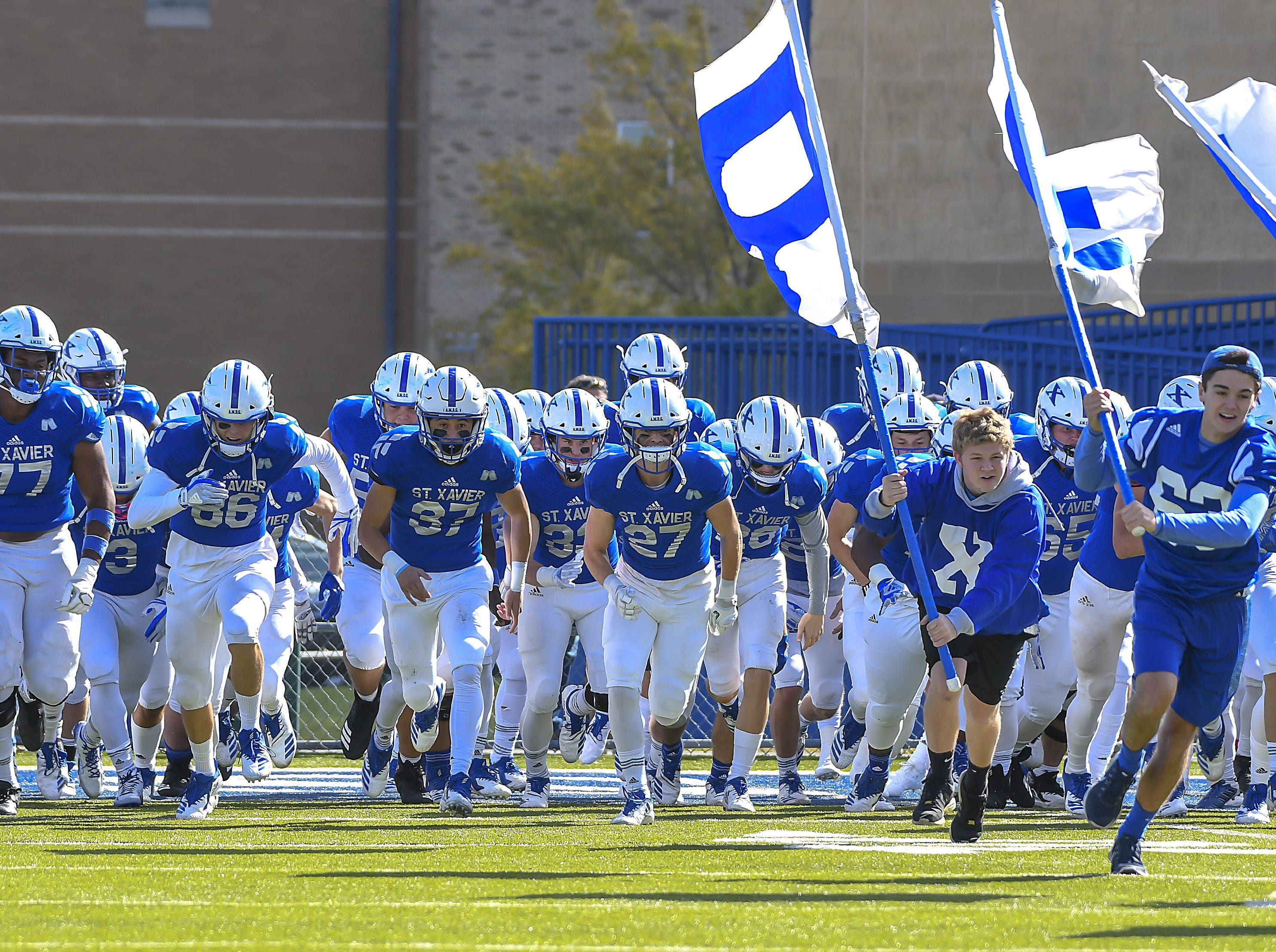 Bomber players run onto the field before their game against Cleveland St. Ignatius at St. Xavier High School, Saturday, October, 20 2018