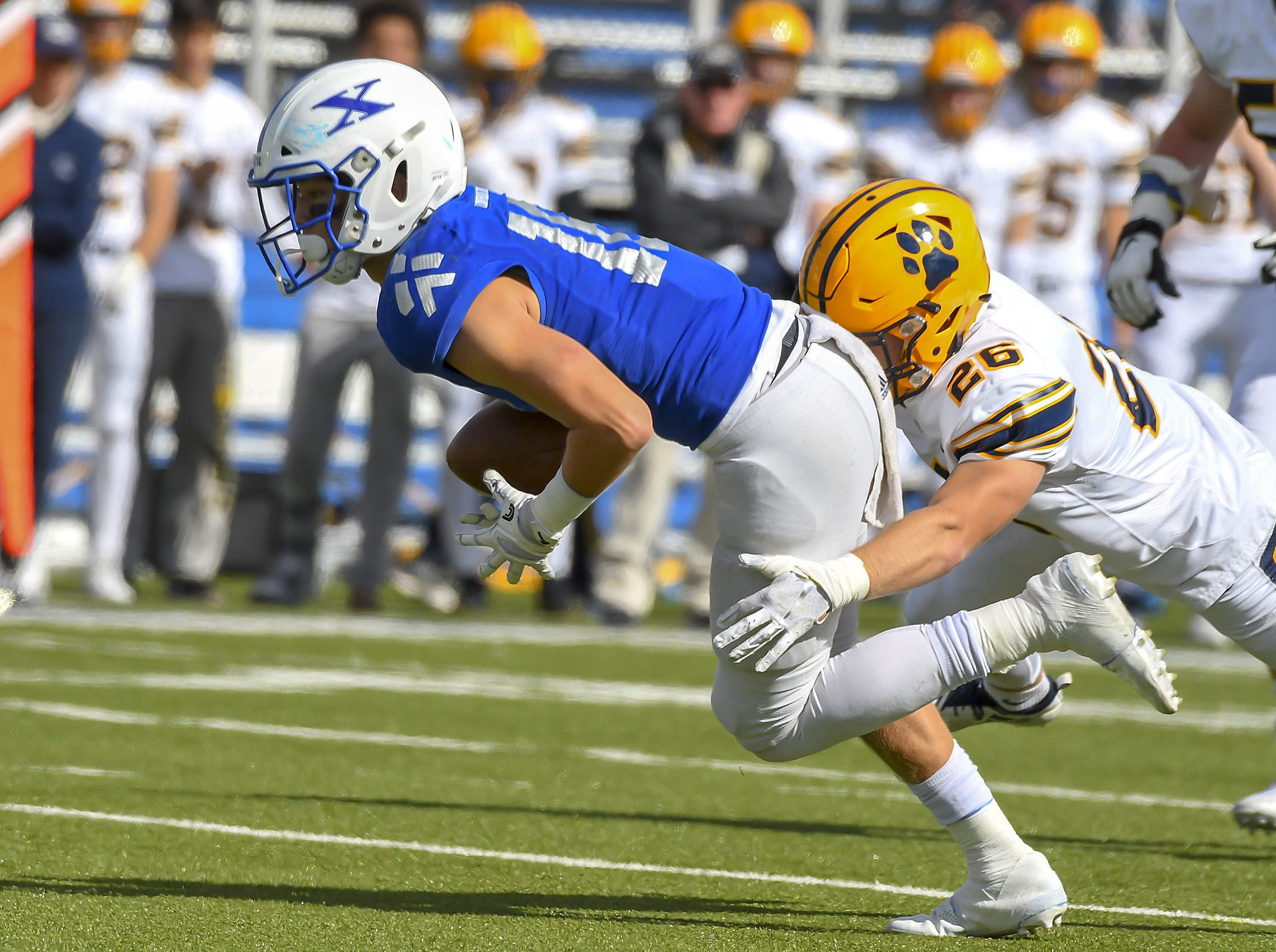 Nathan Stockman of St. X is tackled by a St. I's defender at St. Xavier High School, Saturday, October, 20 2018