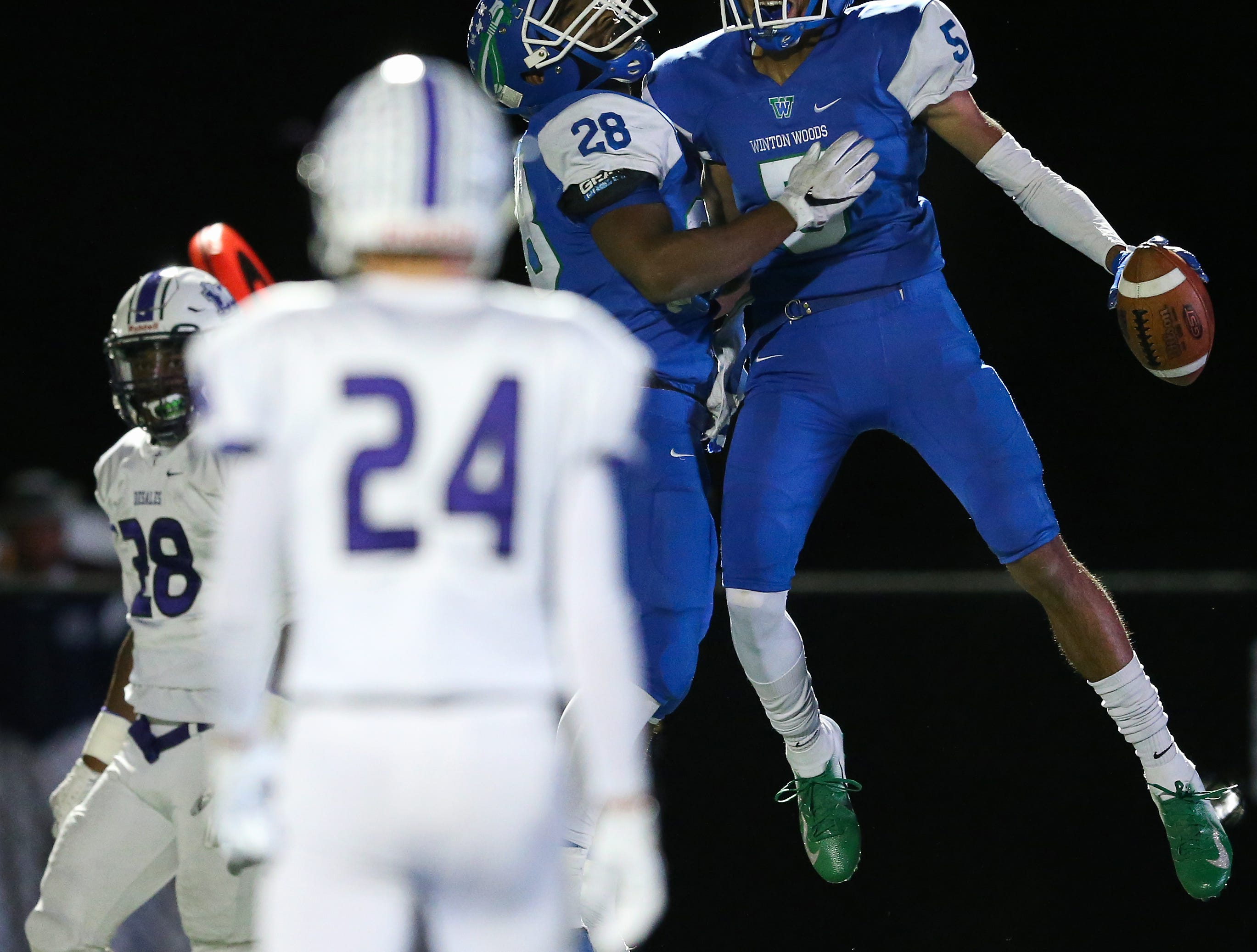 Winton Woods Warriors wide receiver Rashaun Brown (5), far right, celebrates a touchdown catch with running back Miyan Williams (28) in the second quarter during a high school football game between St. Francis de Sales and Winton Woods, Friday, Oct. 19, 2018, at Winton Woods High School in Forest Park, Ohio.