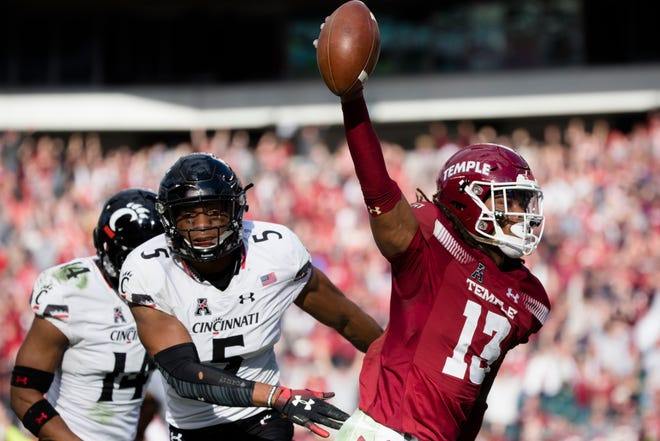 Temple Owls wide receiver Isaiah Wright (13) catches a touchdown in overtime as Cincinnati Bearcats cornerback Cameron Jefferies (14) and Cincinnati Bearcats safety Darrick Forrest (5) guard him during the NCAA football game between Cincinnati Bearcats and Temple Owls on Saturday, Oct. 20, 2018, at Lincoln Financial Field in Philadelphia, Penn.