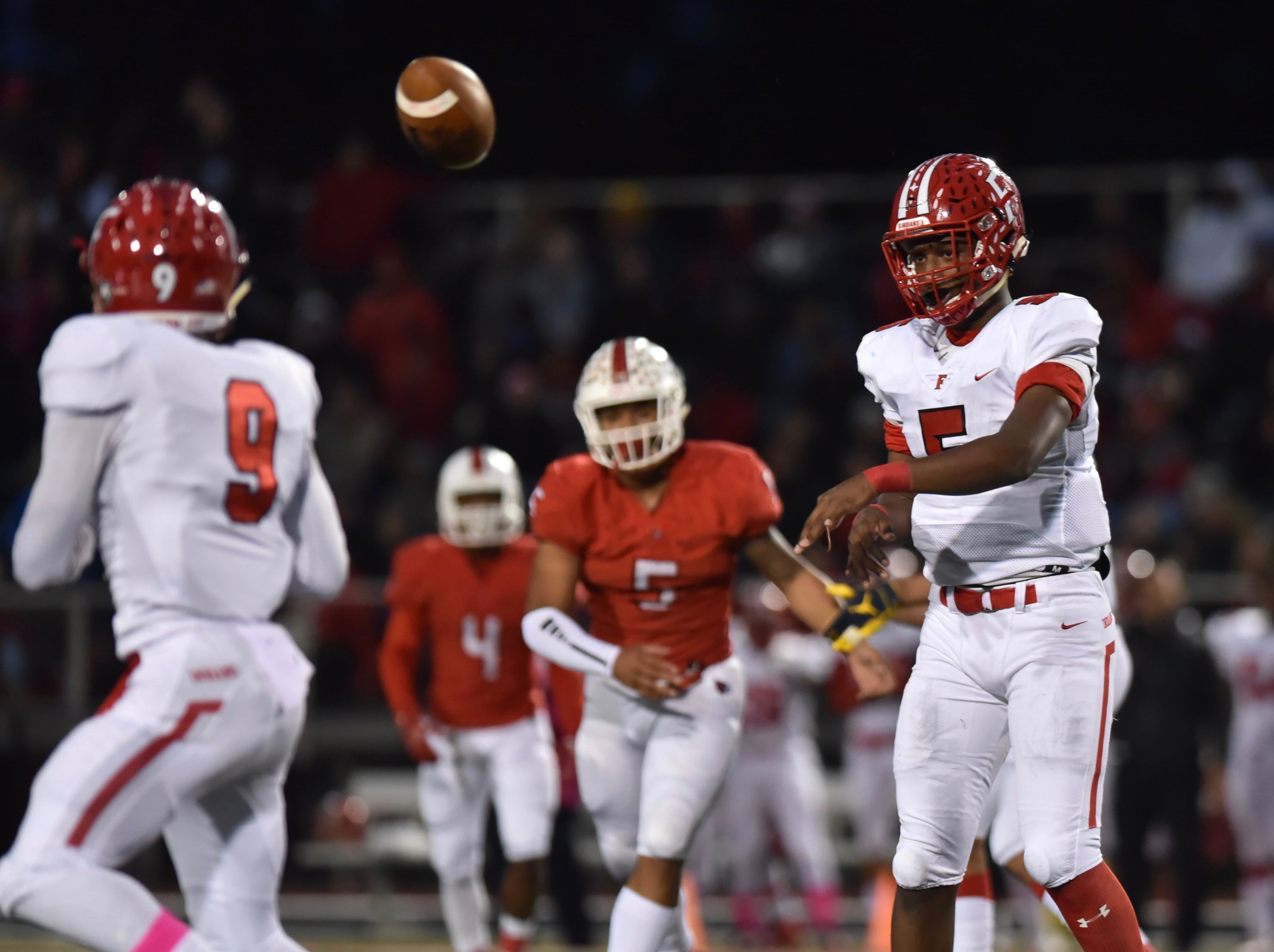 Fairfield's Jeff Tyus passes the ball to Jutahn McClain in the first quarter against Colerain Friday, Oct. 19, 2018 at Colerain High School