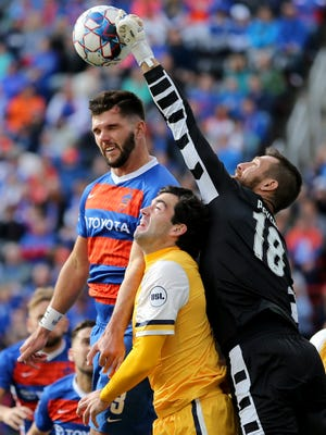 FC Cincinnati defender Forrest Lasso (3) goes up for a header as Nashville SC goalkeeper Matt Pickens (18) clears the ball in the first half during a USL soccer playoff game between Nashville SC and FC Cincinnati,Saturday, Oct. 20, 2018, at Nippert Stadium in Cincinnati.