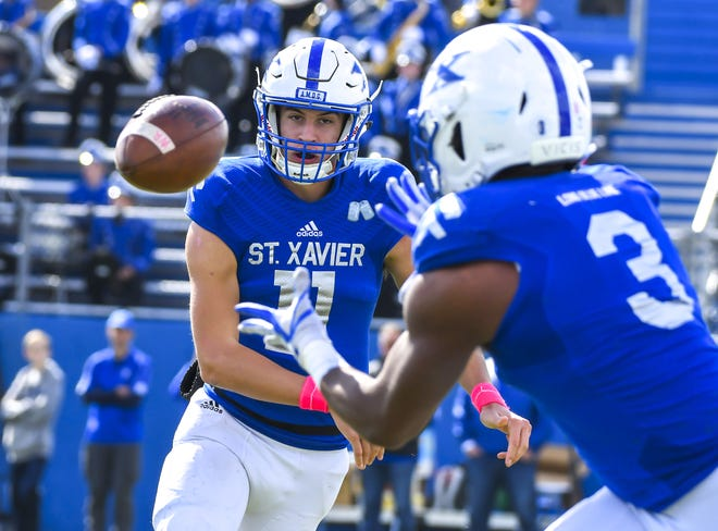 St. X quarterback Wyatt Hudepohl (11) throws a pass to Chris Payne (3) and runs the ball for a 93 yard Bomber touchdown at St. Xavier High School, Saturday, October, 20 2018