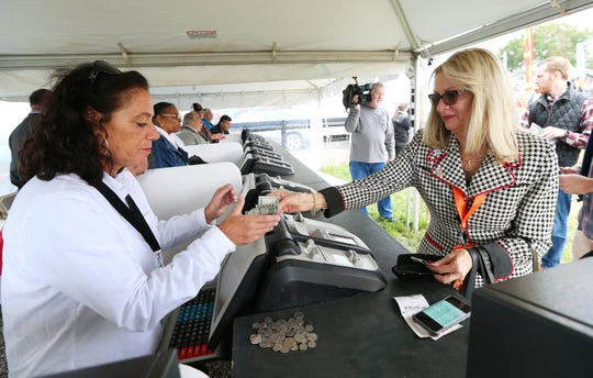 Beverly Torsilieri, right, of Whitehouse Station places her bet during the 98th running of the Far Hills Race Meeting at Moorland Farm in Far Hills, N.J. on Saturday, Oct. 20, 2018.