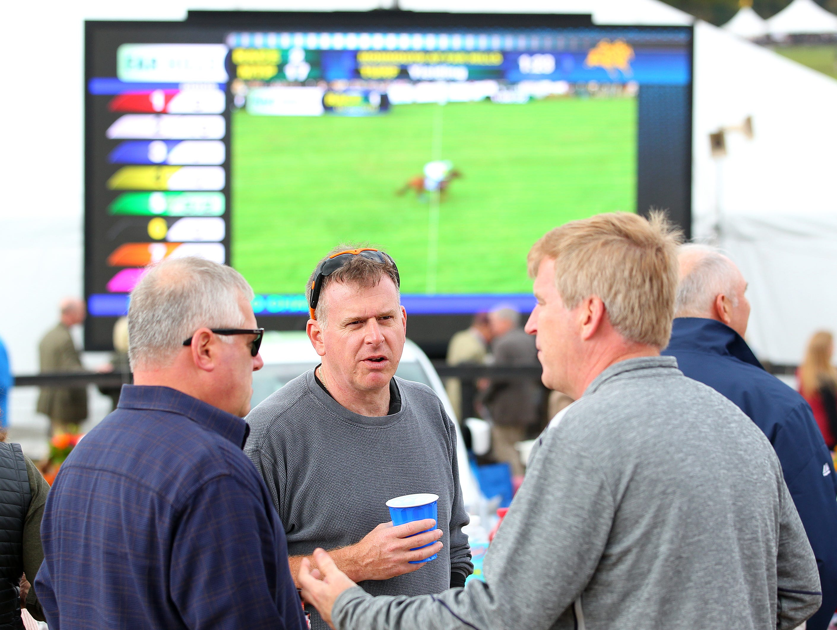 Three spectators talk during the 98th running of the Far Hills Race Meeting at Moorland Farm in Far Hills, N.J. on Saturday, Oct. 20, 2015. Photo by Rich Schultz/ HNT