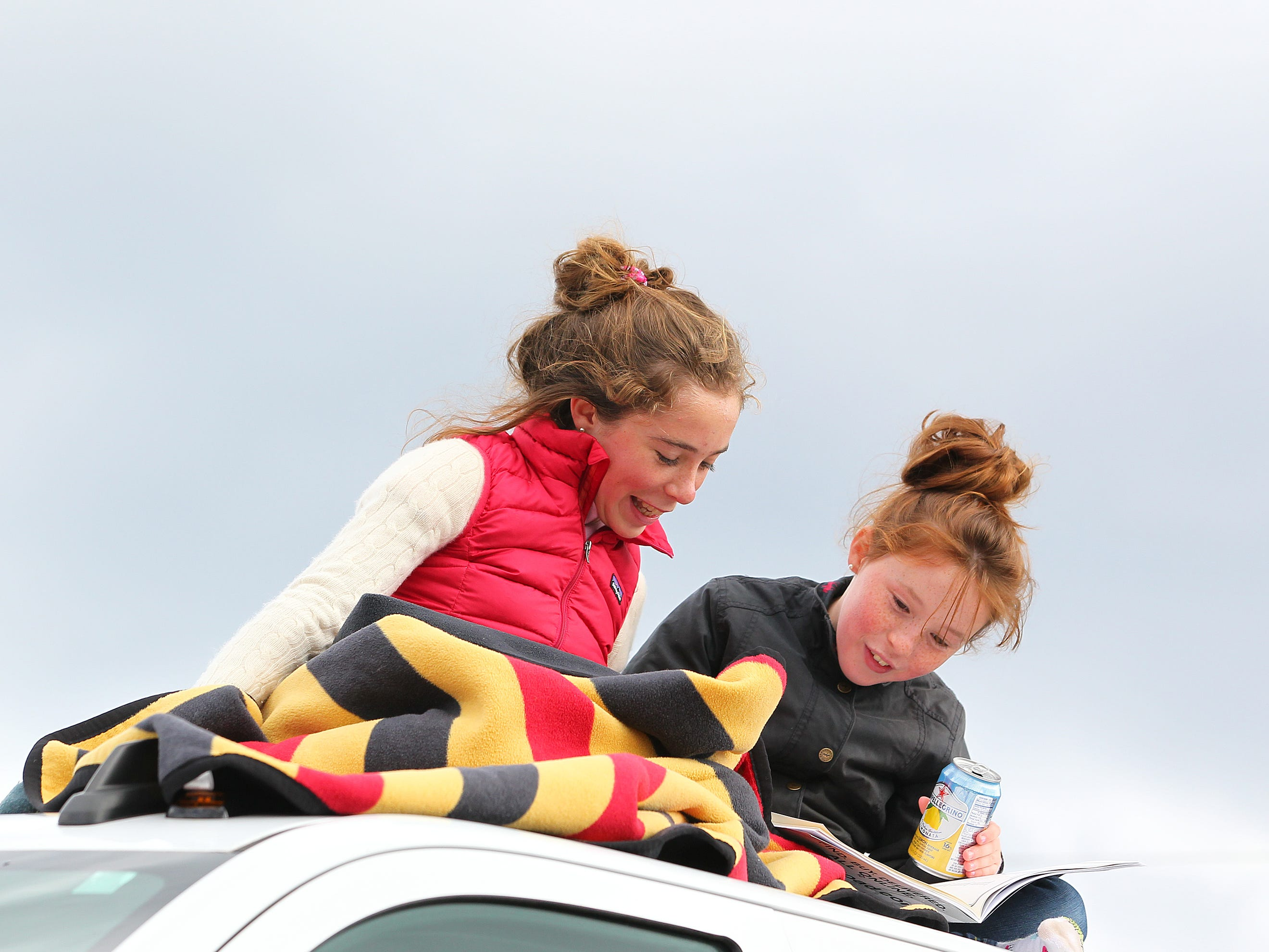Emma, 13 and Gracie Sameth 10 of Far Hills stay warm on the roof of their family car during the 98th running of the Far Hills Race Meeting at Moorland Farm in Far Hills, N.J. on Saturday, Oct. 20, 2015. Photo by Rich Schultz/ HNT