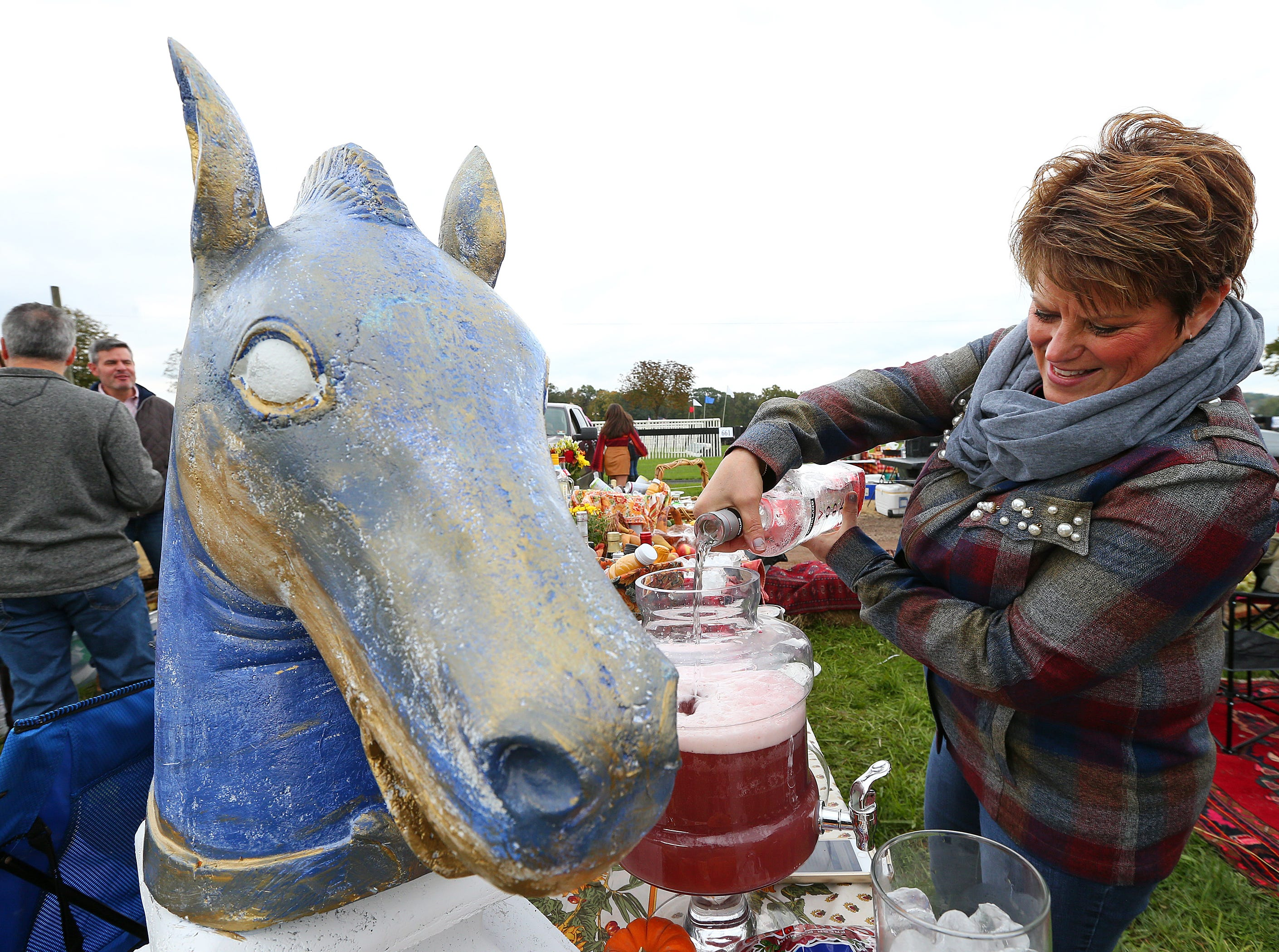 Liz Behring of Ann Arbor, Mi makes a fruit punch during the 98th running of the Far Hills Race Meeting at Moorland Farm in Far Hills, N.J. on Saturday, Oct. 20, 2015. Photo by Rich Schultz/ HNT