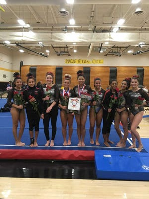 The Bishop Ahr gymnasts pose after winning the 2018 GMC Championship.