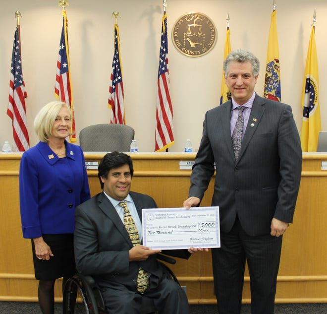 Freeholder Director Patrick Scaglione, center, and Freeholder Patricia Walsh present a ceremonial check to Green Brook Mayor Patrick Boccio, on behalf of the township's Municipal Youth Services Commission.