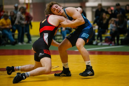 Cael Happel, red, wrestles Wyatt Henson, blue, during their 132 pound match at the Agony in Ames High School Showcase on Saturday, Oct. 20, 2018, in Ames. Henson would go on to win 10-3.