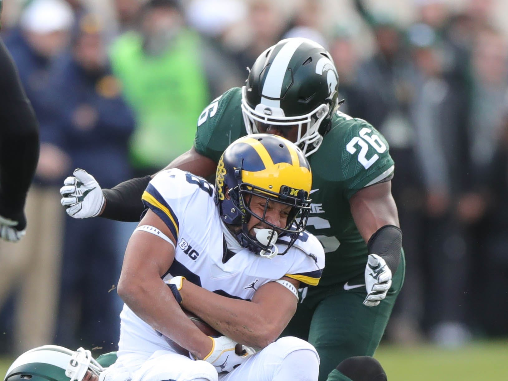 Michigan wide receiver Grant Perry is tackled by Michigan State safety Khari Willis, bottom, and Brandon Bouyer-Randle during the first half on Saturday, Oct. 20, 2018, at Spartan Stadium.