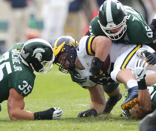 Michigan's Ben Mason is tackled by Michigan State's Jacub Panasiuk, right, and Joe Bachie, left, Oct. 20, 2018, at Spartan Stadium.