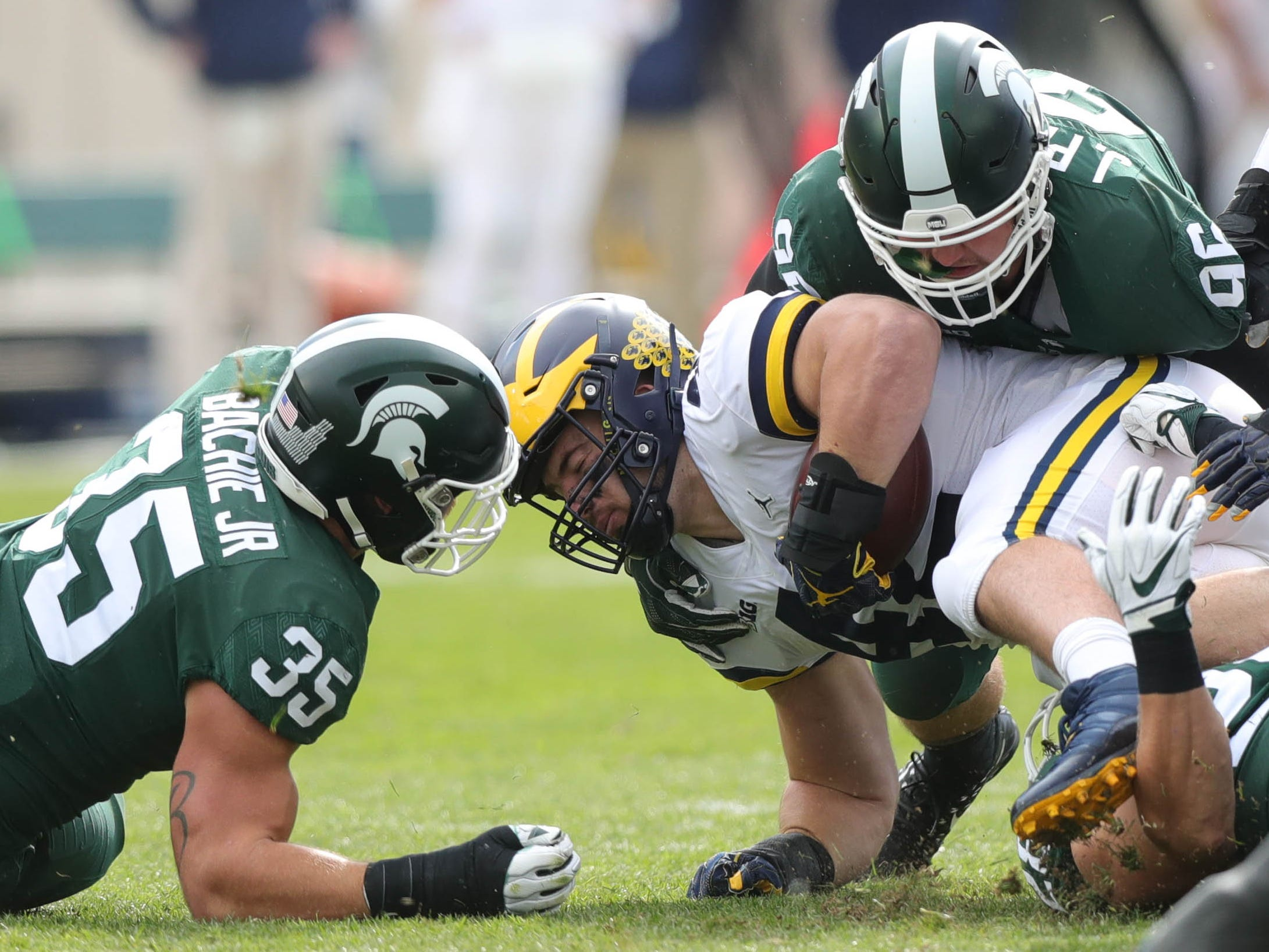 Michigan fullback Ben Mason is tackled by Michigan State's Jacub Panasiuk during the first half on Saturday, Oct. 20, 2018, at Spartan Stadium.