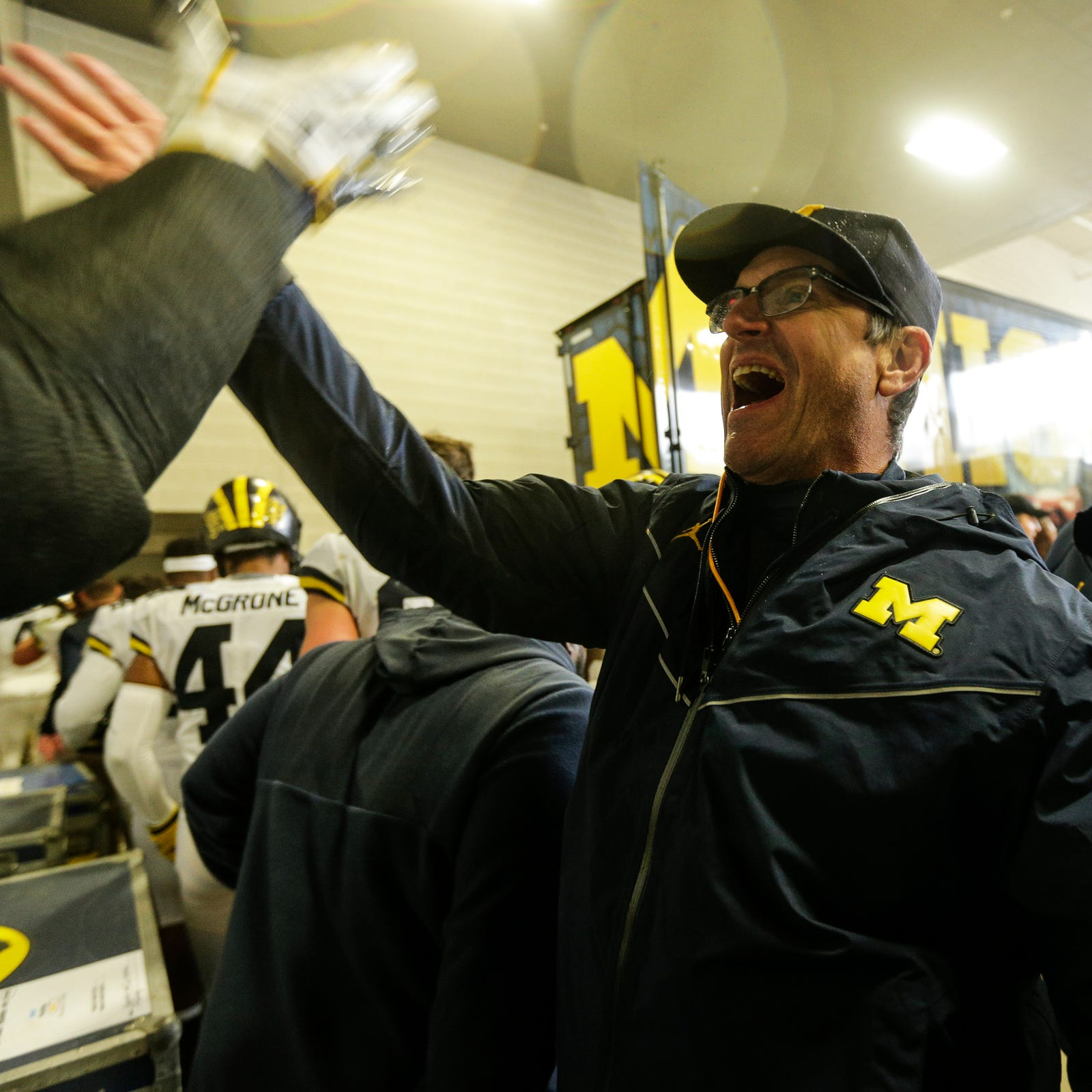 Michigan head coach Jim Harbaugh high-fives players and coaches at the end of the tunnel after the 21-7 win over Michigan State on Spartan Stadium in East Lansing, Saturday, Oct. 20, 2018.