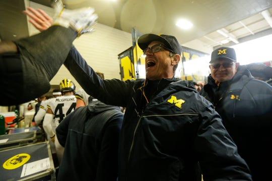 Jim Harbaugh high-fives players and coaches at the end of the tunnel after Michigan's 21-7 win.