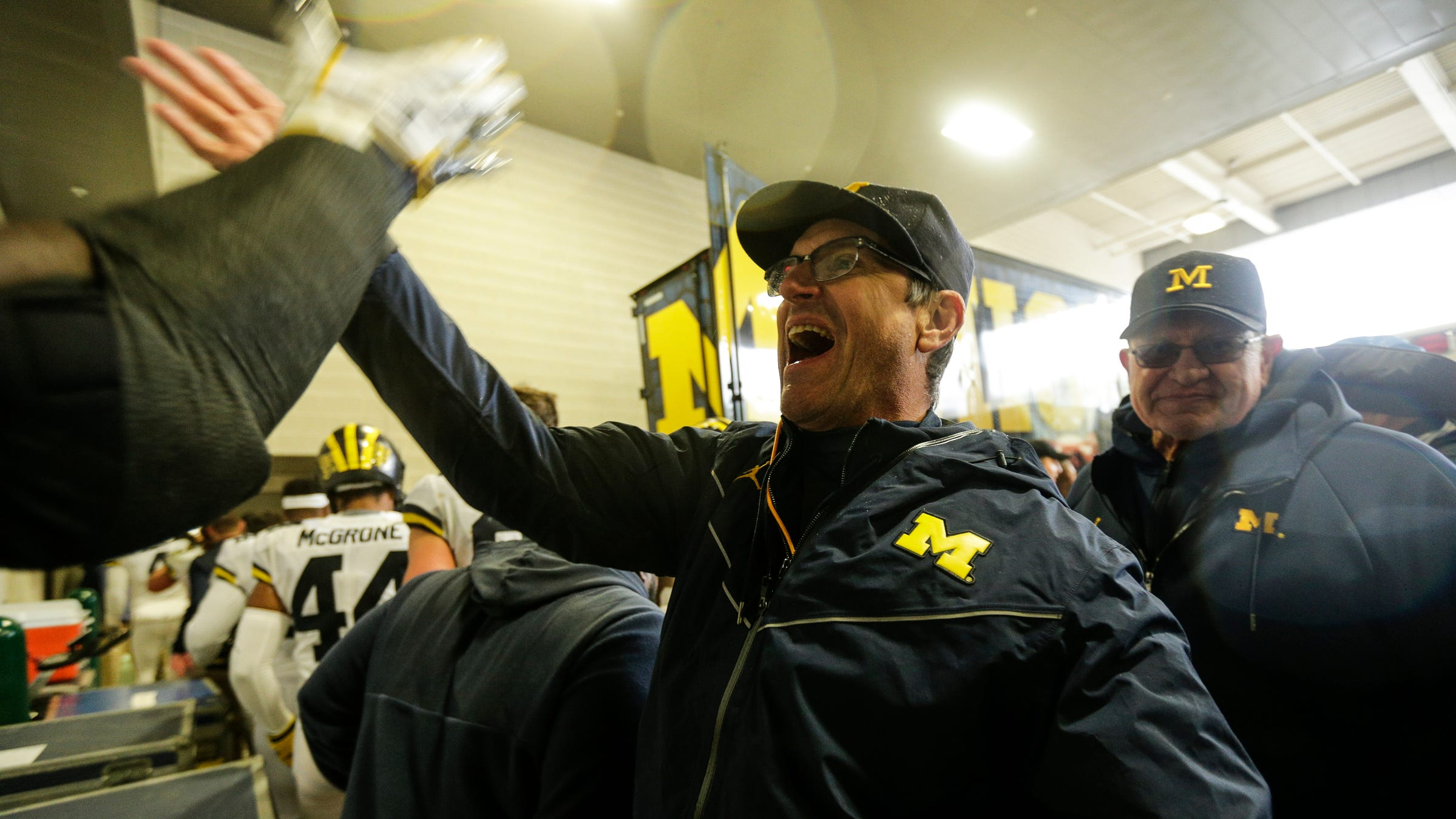 Michigan coach Jim Harbaugh high-fives players and coaches at the end of the tunnel after the 21-7 win over Michigan State on Spartan Stadium in East Lansing, Saturday, Oct. 20, 2018.