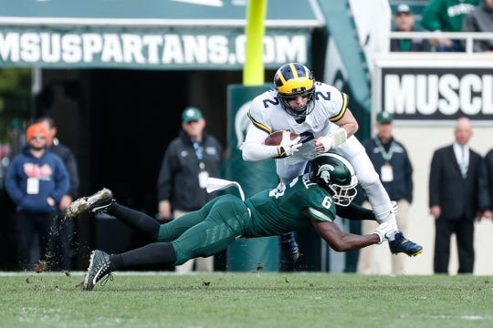 Michigan quarterback Shea Patterson is tackled by Michigan State safety David Dowell during the first half at Spartan Stadium on Saturday, Oct. 20, 2018.