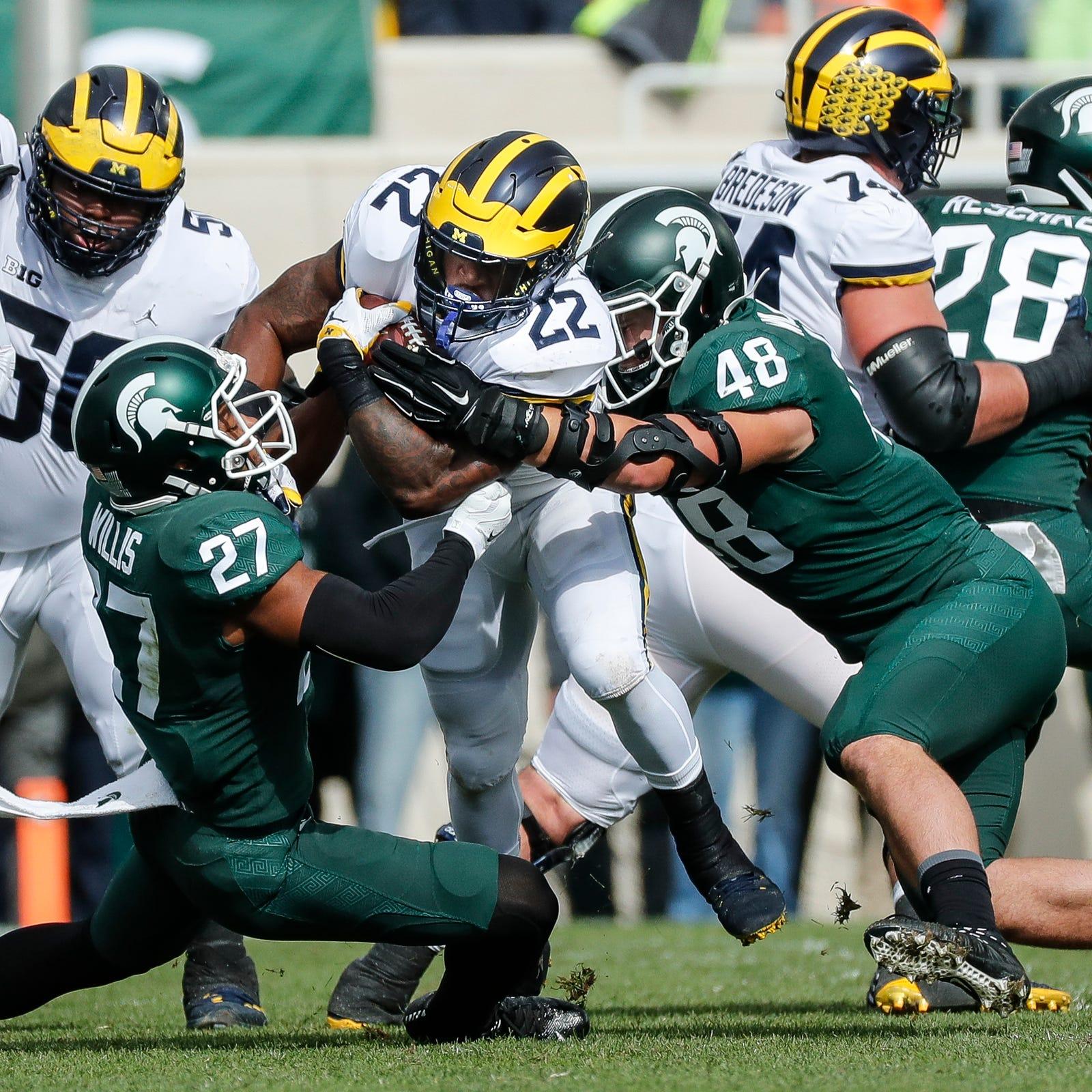 Michigan running back Karan Higdon runs against Michigan State safety Khari Willis, left, and defensive end Kenny Willekes during the first half at Spartan Stadium on Saturday, Oct. 20, 2018.