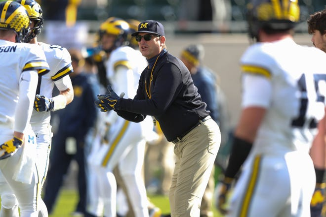 Michigan head coach Jim Harbaugh warms up his team before action against Michigan State on Saturday, Oct. 20, 2018, at Spartan Stadium.