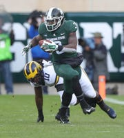 Michigan State running back LJ Scott runs by Michigan linebacker Devin Bush during the first half on Saturday, Oct. 20, 2018, at Spartan Stadium.