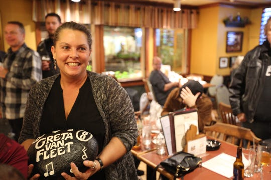 "Karen Kiszka, mother of three Greta Van Fleet band members, shows off the painted rock given to her at a party for the band's ""Anthem of the Peaceful Army"" in Frankenmuth, Mich., on Oct. 19, 2018."