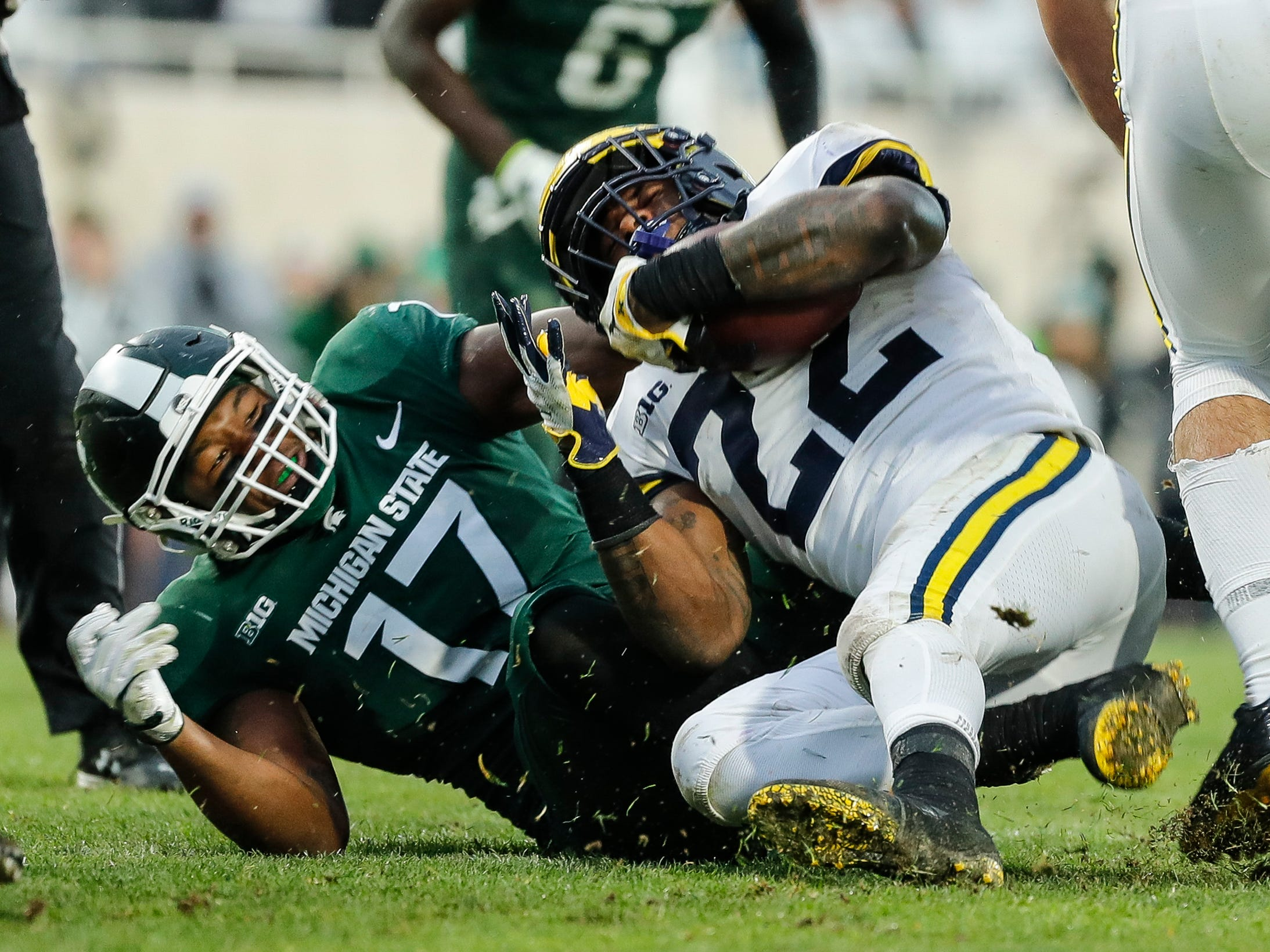 Michigan running back Karan Higdon is stopped by Michigan State linebacker Tyriq Thompson during the second half at Spartan Stadium in East Lansing, Saturday, Oct. 20, 2018.