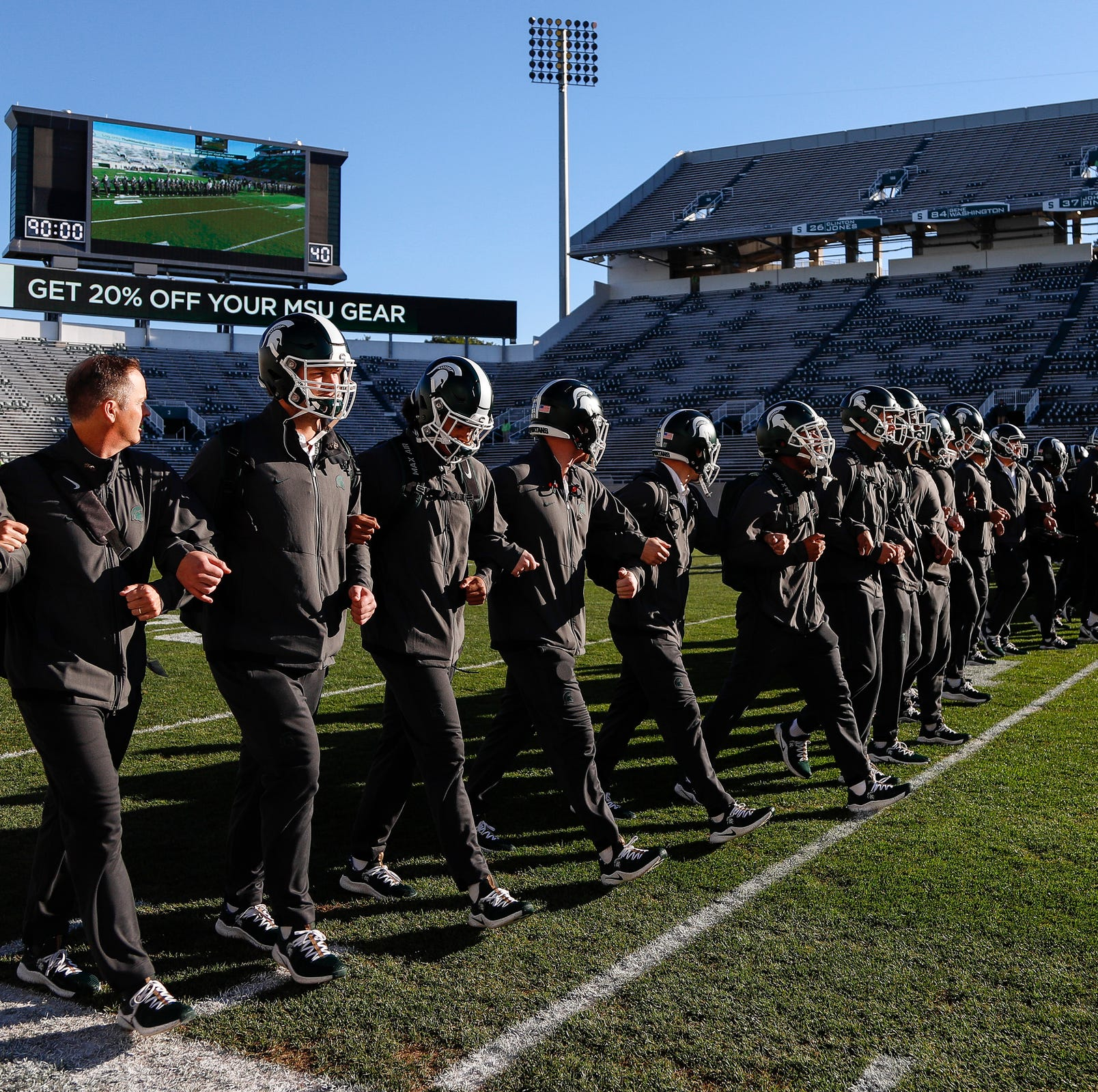 Michigan State football players lock arms and walk across the field before the Michigan game at Spartan Stadium in East Lansing on Sat., October 20, 2018.