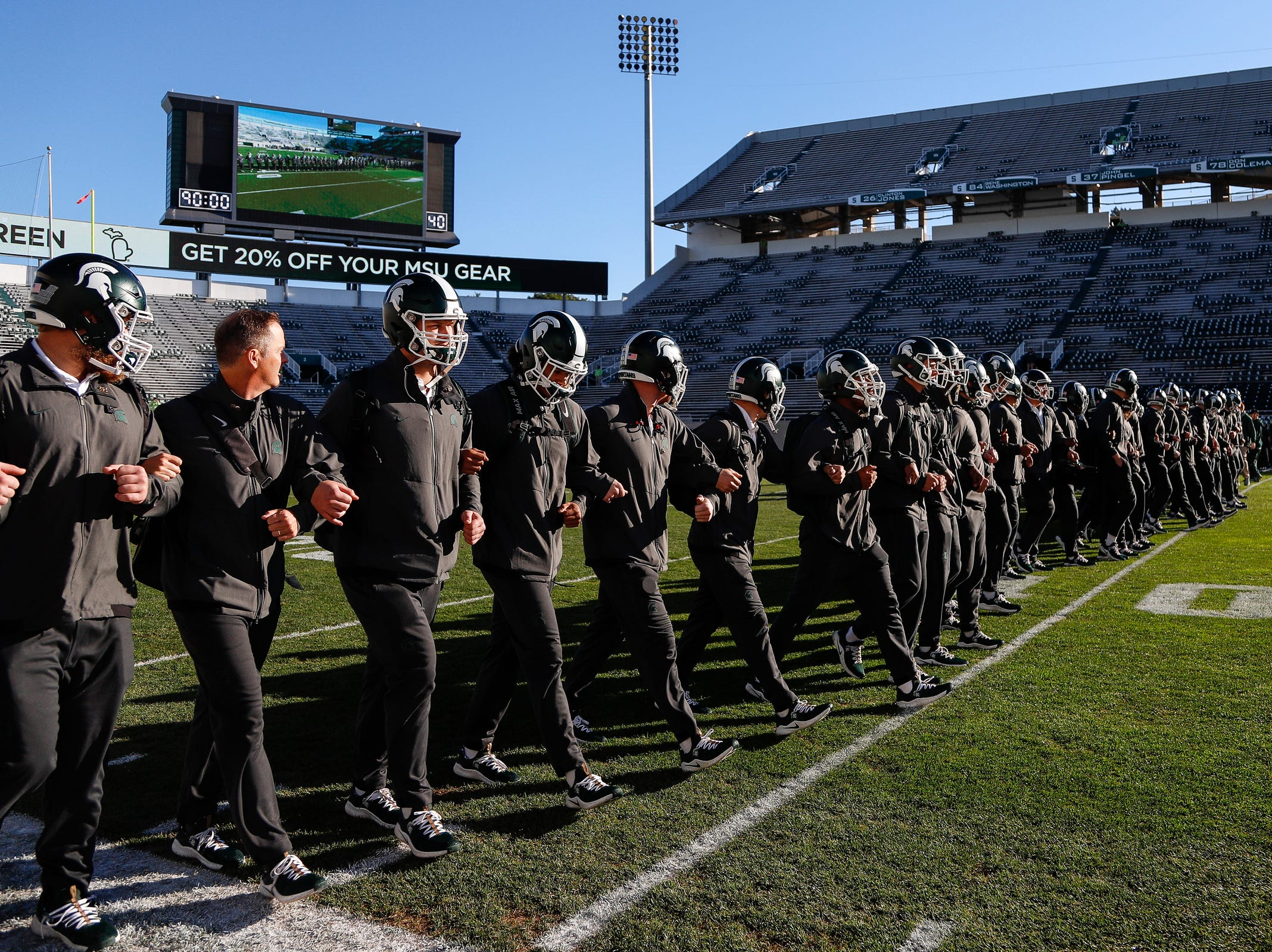 Michigan State players lock arms and walk across the field before the Michigan game at Spartan Stadium on Sat., October 20, 2018.