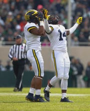 Michigan safety Josh Metellus, right, and linebacker Khaleke Hudson celebrate a stop against Michigan State during the first half in Spartan Stadium on Saturday, Oct. 20, 2018.